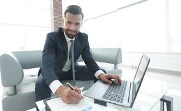 Stylish man working on laptop and making notes in notebook. Photo with copy space Royalty Free Stock Image