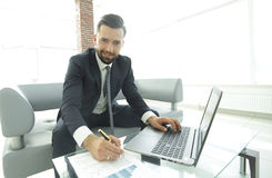Stylish man working on laptop and making notes in notebook. Photo with copy space Royalty Free Stock Photos