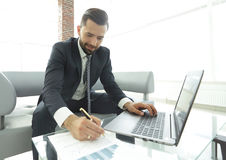 Stylish man working on laptop and making notes in notebook. Photo with copy space Stock Photography