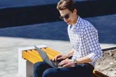 Stylish man working on laptop at street. Outside Royalty Free Stock Image