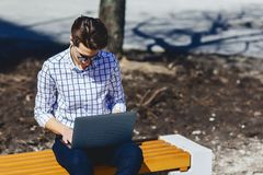 Stylish man working on laptop at street. Outside Stock Photography