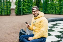 Stylish man in yellow anorak, balck cap and eyeglasses resting with smartphone while sitting outdoors in park. Handsome man with a. Ppealing appearance typing stock photos