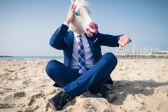 Stylish manager in comical mask and elegant suit. Sits on beach and looks on the watch. Scared man lost in time and is late for business Stock Image