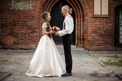 Stylish married couple standing and smiling in the background of old building arch. Stylish married couple standing and smiling in the background of old red royalty free stock photos