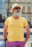 Stylish mature bearded man in bright yellow t-shirt and hat Royalty Free Stock Photo