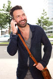 Stylish mature man talking on cell phone outdoors. Portrait of stylish mature man standing outdoors and talking on cell phone Stock Image