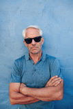 Stylish mature man wearing sunglasses. Portrait of stylish mature man wearing sunglasses standing with his arms crossed against blue background Stock Photos