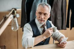 Stylish mature tailor drinking coffee and using smartphone. At sewing workshop stock image