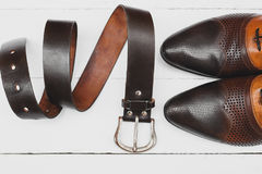Stylish men`s shoes and belt on white Royalty Free Stock Images