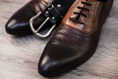 Stylish men`s shoes and belt. On wooden background Stock Photo