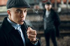 Stylish men smoking in retro clothes posing on background of railway. england in 1920s theme. fashionable look of brutal. Stylish man smoking in retro clothes royalty free stock image