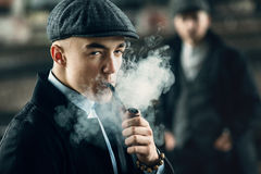 Stylish men smoking in retro clothes posing on background of rai Stock Photo