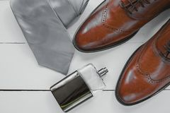 Stylish mens accessories. Brown shoes with cuff, tie and perfume Royalty Free Stock Photography