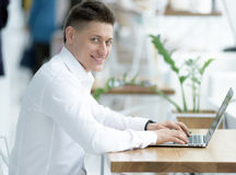 Stylish middle-aged businessman looking at camera with toothy smile while working on project in cozy small cafe Royalty Free Stock Images