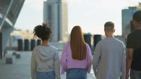 Stylish millennial walking city street together, teenage unity, togetherness