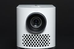 Stylish mini home cinema LED projector, lightweight tech gadget. Front view stock photography