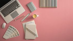 Stylish minimal office table desk. Workspace with laptop, notebook, pencils, coffee cup and sample color palette on pastel pink ba royalty free stock images