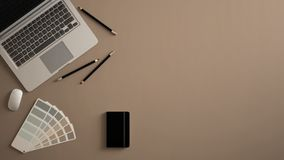 Stylish minimal office table desk. Workspace with laptop, notebook, pencils and sample color palette on beige background. Flat lay royalty free stock photography