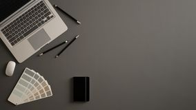 Stylish minimal office table desk. Workspace with laptop, notebook, pencils and sample color palette on gray background. Flat lay, royalty free stock photos