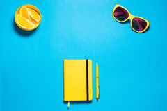 Stylish minimalistic feminine fashion workspace. Bright yellow glasses and diary with pen, pirces oranges against deep Stock Image
