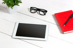 Stylish minimalistic workplace with tablet and notebook and glasses in flat lay style. White background. Top view. Copy space royalty free stock photos
