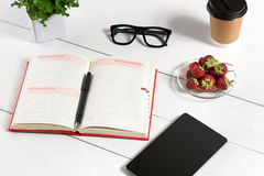 Stylish minimalistic workplace with tablet and notebook and glasses in flat lay style. White background. Top view. Copy space stock images