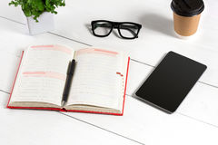 Stylish minimalistic workplace with tablet and notebook and glasses in flat lay style. White background. Top view. Copy space royalty free stock image
