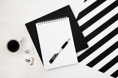 Minimalistic workspace with book, notebook, pencil, cup of coffee on striped black and white background. Flat lay style Top view Royalty Free Stock Image