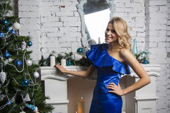 Stylish model in blue silk dress near new year tree Royalty Free Stock Photo