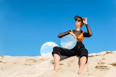 Stylish model posing on dune with round mirrors with reflection of. Blue sky royalty free stock image