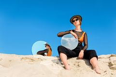 Stylish model posing with round mirrors with reflection of. Blue sky royalty free stock photography