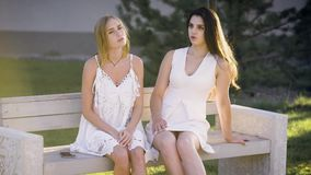 Stylish models in white dresses posing on bench in park and talking lively. stock video footage