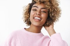 Stylish modern african-american girlfriend looking joyful and delighted at camera raising head proudly and smiling. Laughing out loud touching curls on back stock images