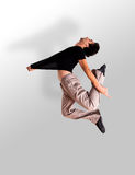 Stylish modern ballet dancer jumping. On grey Stock Photography