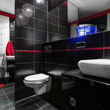 Stylish and modern bathroom. Spacious, stylish and modern bathroom in black with red details, white basin and toilet Royalty Free Stock Photography