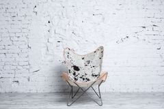 Stylish modern chair with animal print in loft interior. Stylish modern chair with animal print against white brick wall. Loft interior concept Royalty Free Stock Photography