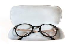 Stylish modern fashionable elegant black eyeglasses in white lea. Ther case. Indoors horizontal close-up image Stock Photos