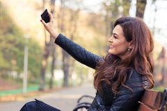 Stylish modern girl taking a selfie. With smart phone in autumn park stock image