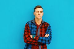 Stylish modern handsome young man in a multi-colored fashionable plaid shirt with hairstyle in a t-shirt posing outdoors. In the city on a blue background. Cool stock photography