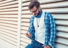 Stylish modern hipster man using smartphone outdoors Stock Photos