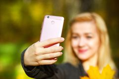 Portrait of cheerful young woman with autumn leafs in front of foliage making selfie stock images