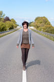 Stylish modern young woman walking along a road Stock Image