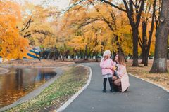 Stylish mohter and child girl 5-6 year old wearing trendy pink coat in autumn park. The girl is dressed in a pink beret. royalty free stock image