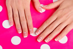 Stylish moon french manicure on a bright pink background. Stylish moon french manicure on a bright pink background with polka dots stock photos