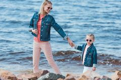 Stylish mother and child in sunglasses holding hands and walking. On sea shore stock image