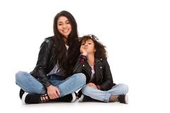 Stylish mother and daughter in leather jackets sitting on floor. Isolated on white Stock Images