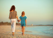 Stylish mother and daughter on seacoast in evening walking. Seen from behind stylish mother and daughter on the seacoast in the evening walking royalty free stock images