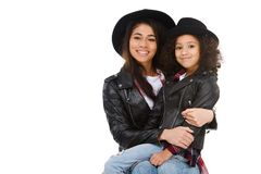 Stylish mother and daughter in similar clothes embracing. Isolated on white royalty free stock image