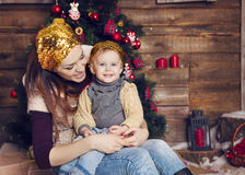 Stylish mother and her child celebrating christmas in room over Stock Photo