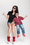 Stylish mother and son. Happy cheerful family, mother and her toddler boy posing in studio wearing sunglasses Royalty Free Stock Image